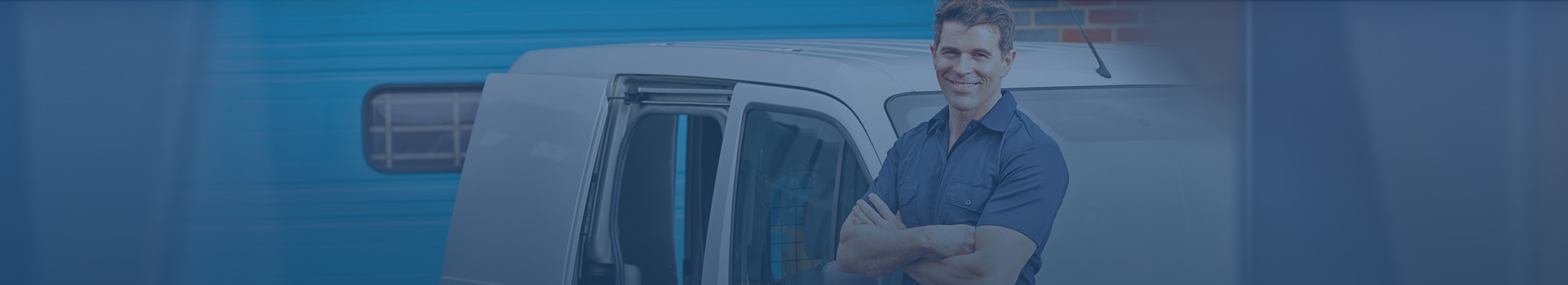 Plumber in blue shirt leaning against van with arms crossed smiling