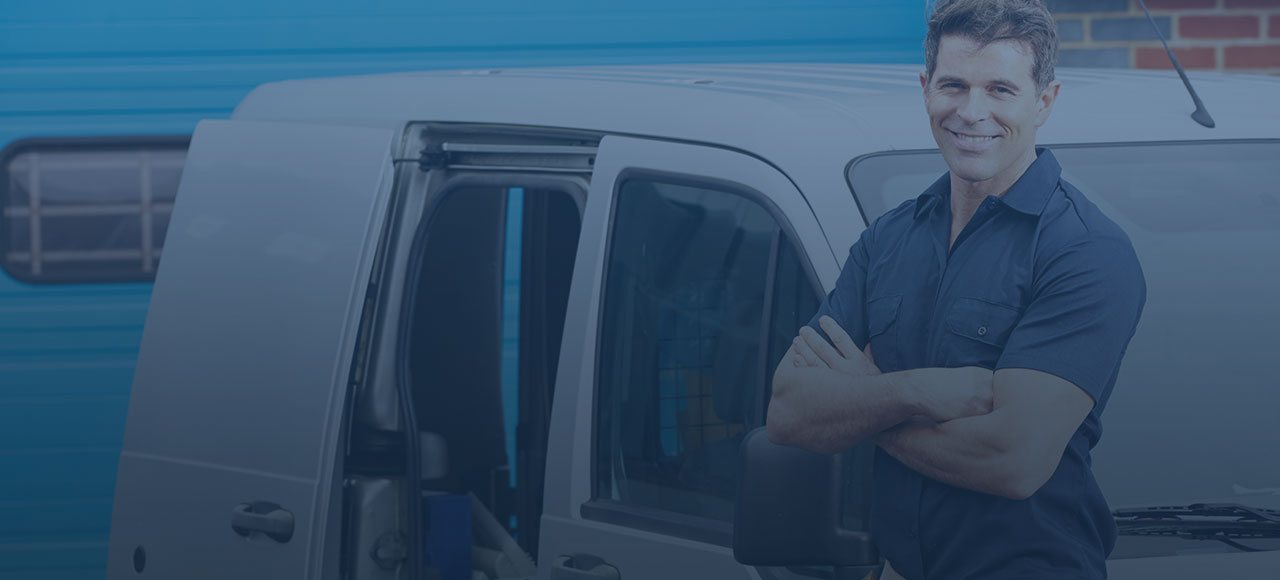 Man in blue shirt smiling leaning against van with arms crossed