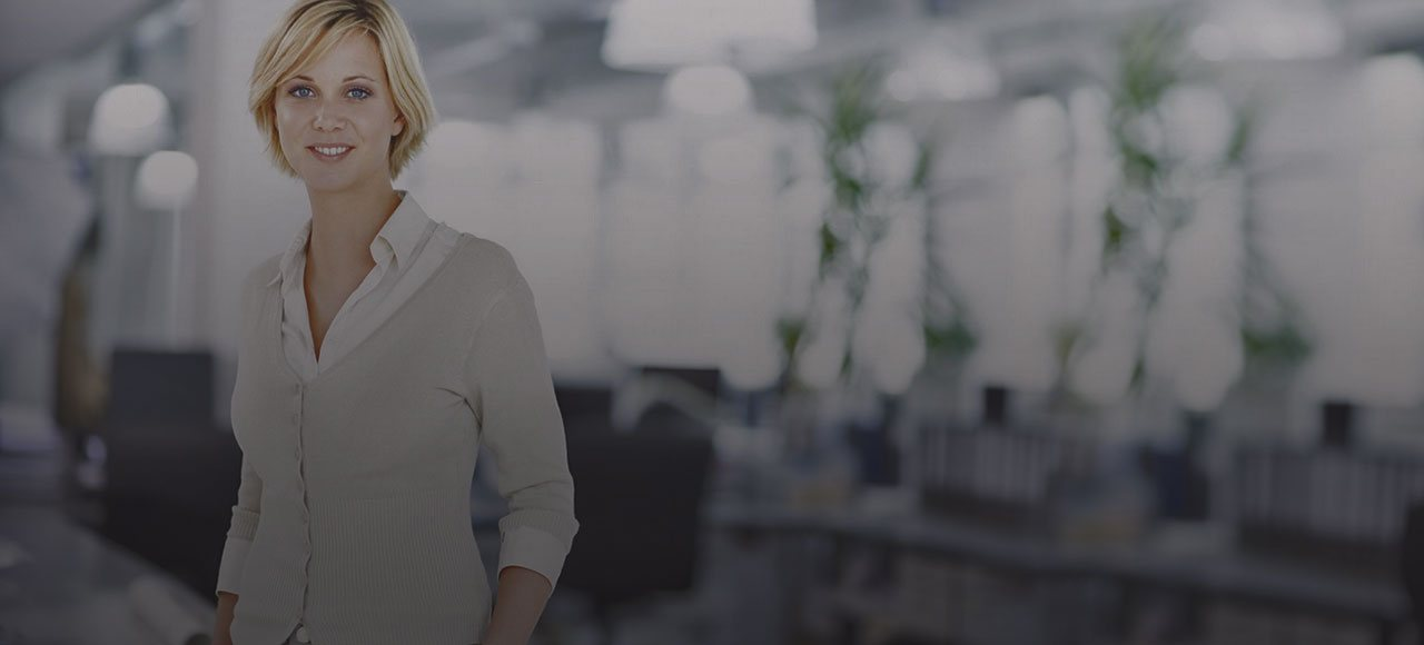 Blonde Woman with short hair smiling in white button shirt in office