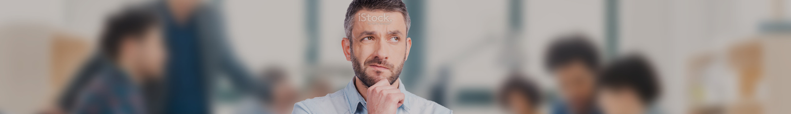 Man with beard in office with fist on chin thinking about questions