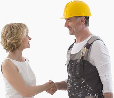 Blonde woman with short hair wearing white sleaveless top shaking hands with contractor wearing overalls, white shirt and yellow hard hat